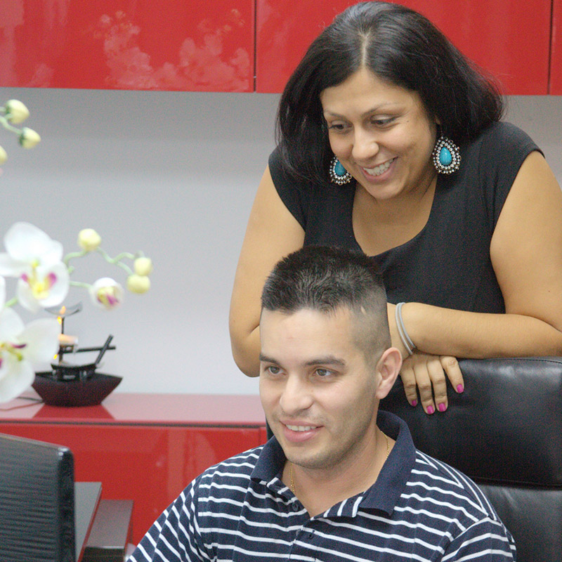 A man sitting and working on a computer, there is a woman behind him smiling, she is leaning over his chair and looking at the computer screen with him