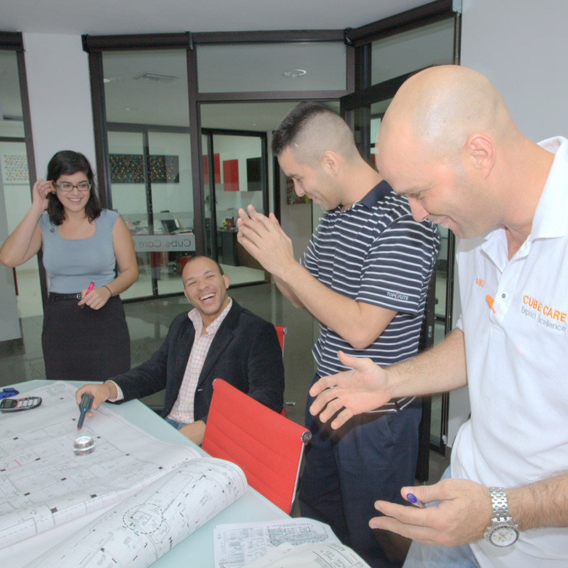 Four people inside of an office, they are happy and celebrating