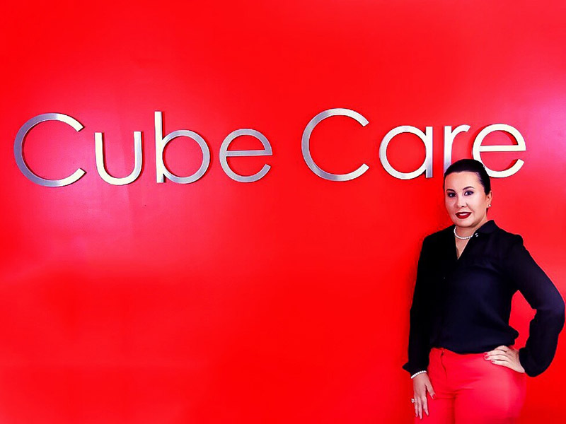 A woman standing next to a sign that reads Cube Care, she has on a black blouse, red pants, and her hair is pulled back