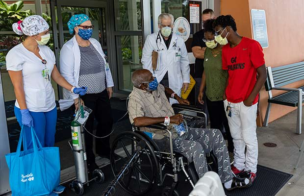 Elderly male in a wheelchair surrounded by family and medical staff