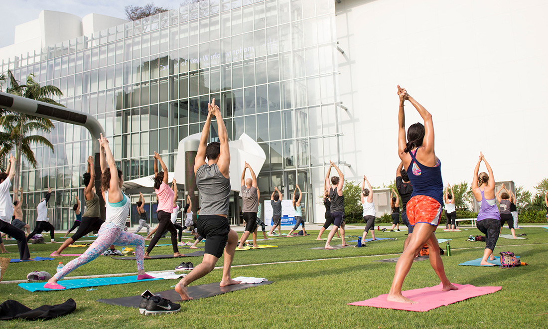 Group of people doing yoga outside on grass