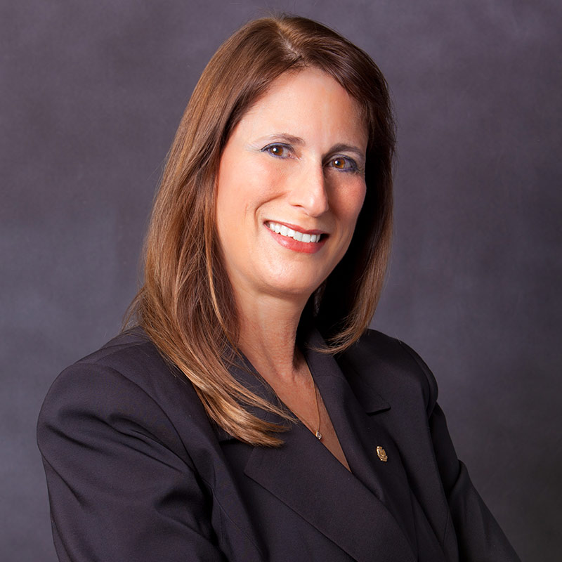 Woman smiling and looking at the camera, she has long brown hair and is wearing a dark suit jacket