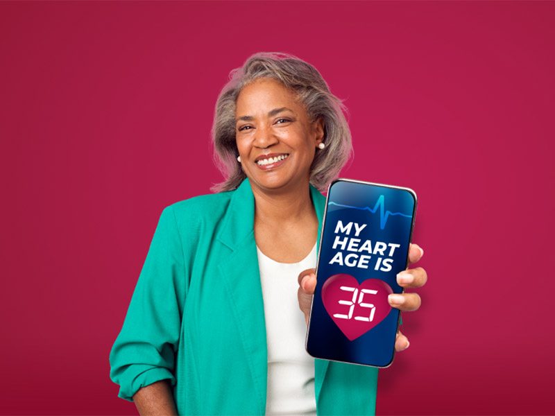 Middle aged woman holding a mobile phone that reads my heart age is 35