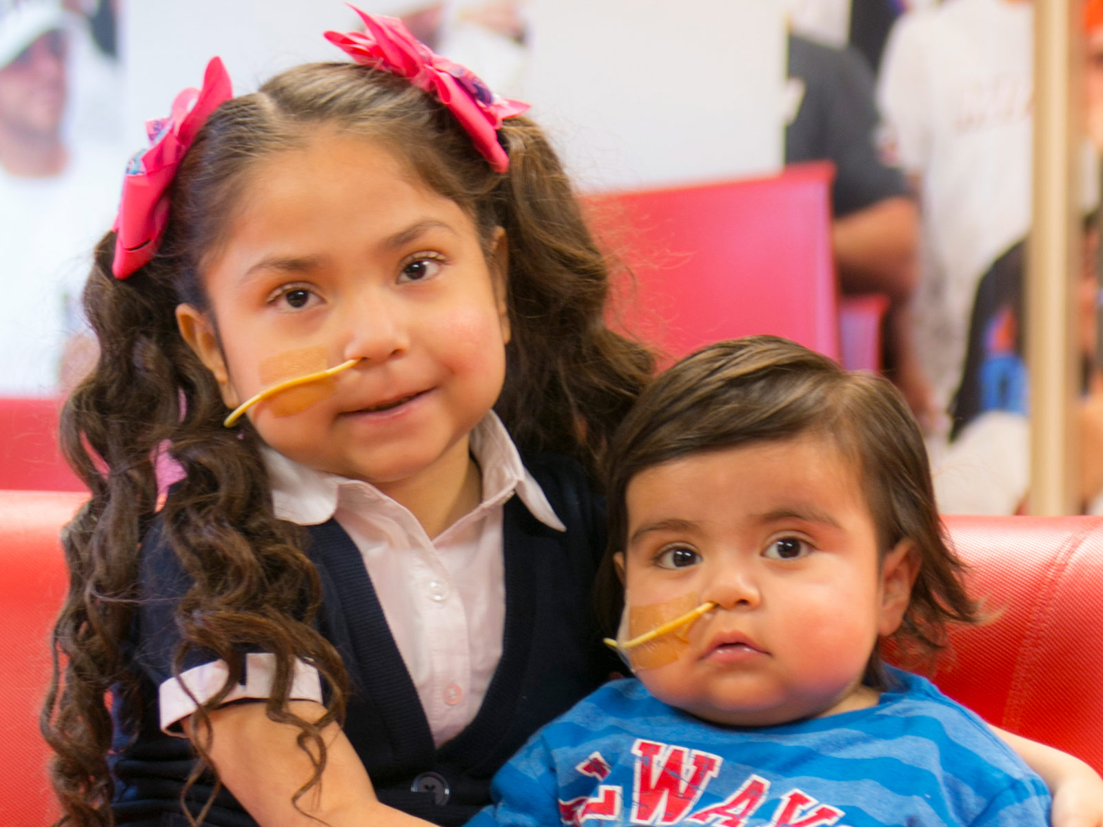 Two young children sitting next to each other, they have a tube coming out of their noses, they both look at the camera