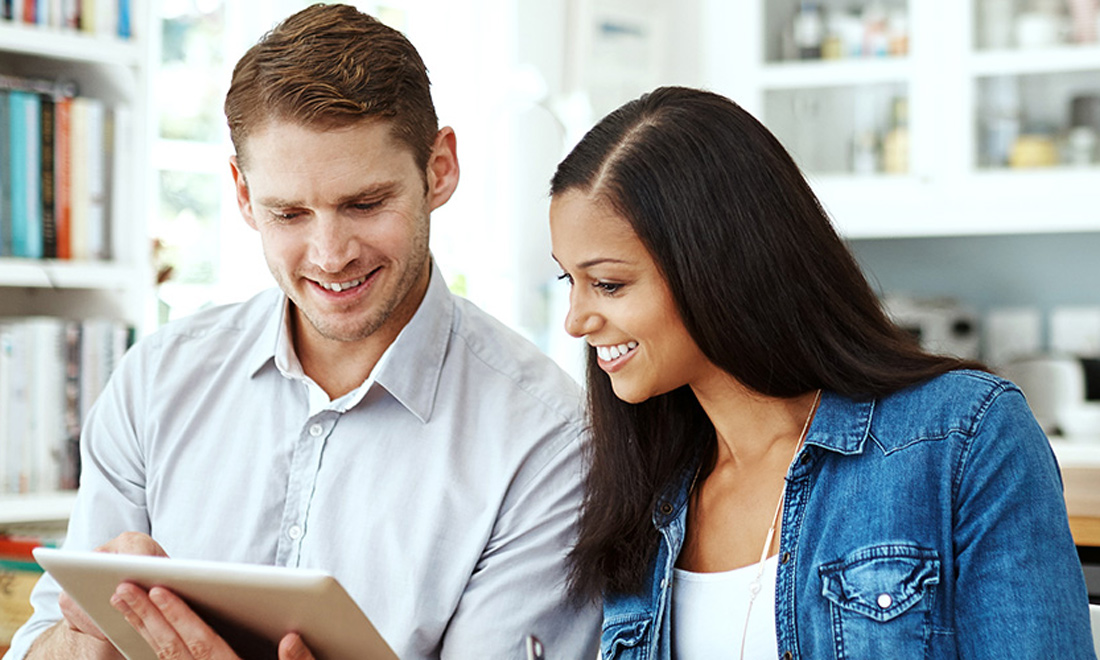 A smiling man and woman review information on a tablet.
