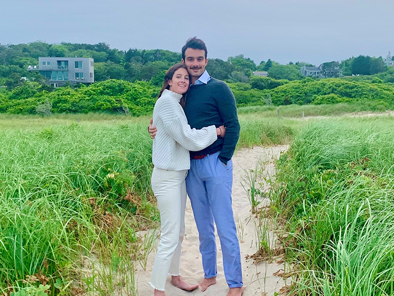 A man and woman hugging on a beach, they are looking into the camera, they are wearing sweaters and pants