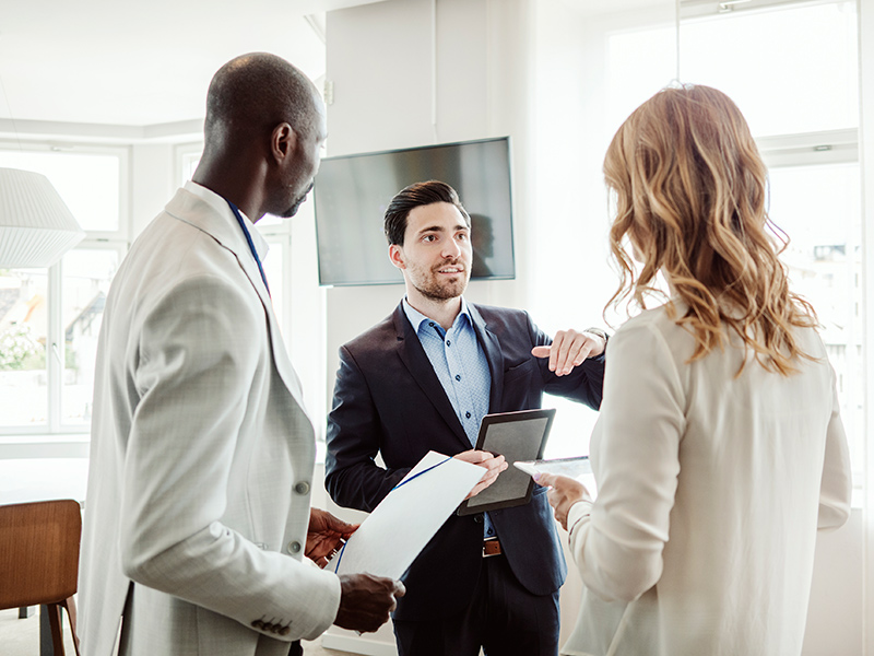Three business people standing and speaking to each other