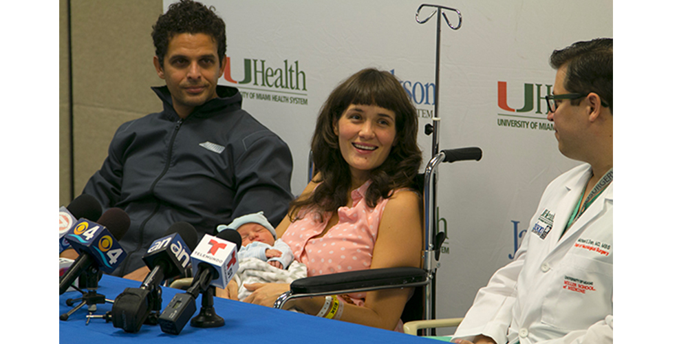 Maria and her husband at a press conference, looking at a doctor.