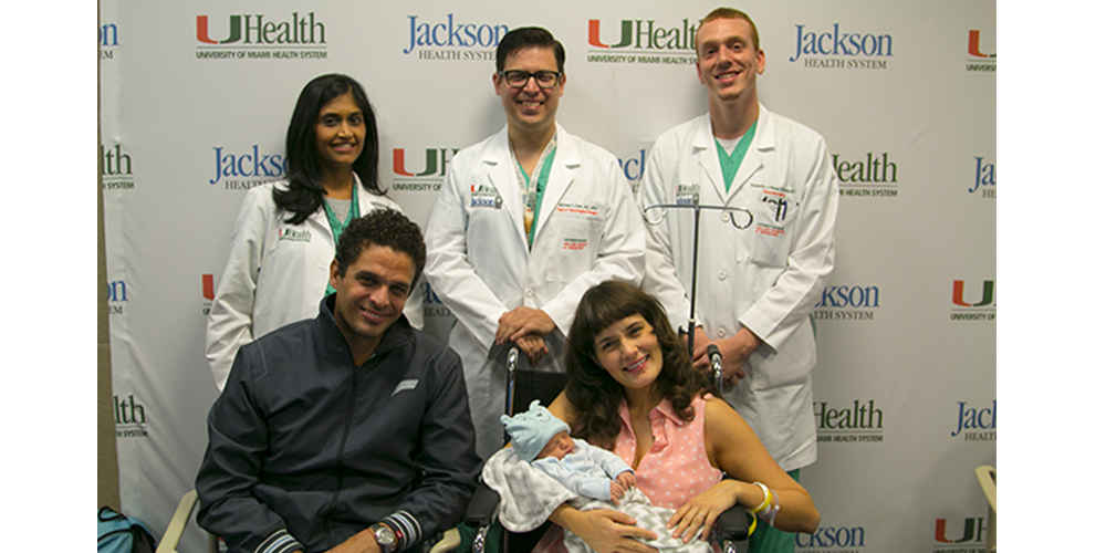 Maria, her husband, and a team of doctors smiling at the camera.