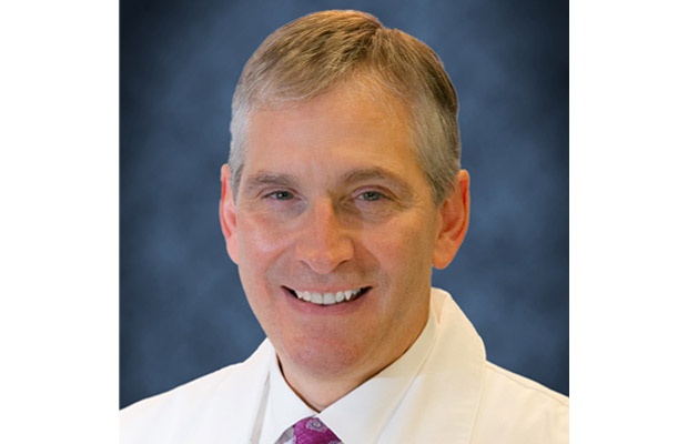 A closeup of a physician, he is smiling at the camera, he has on a white coat and a purple tie