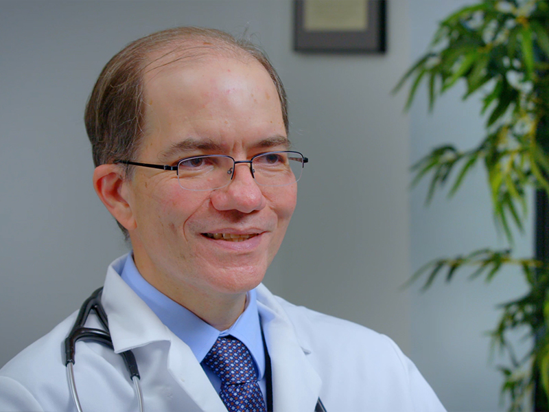 Closeup of a physician, he is looking towards his left, he has on glasses, a white coat, a blue dress shirt, and a purple tie