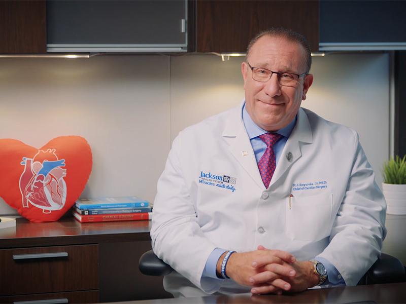 Dr. Segurola sitting behind a desk, he is smiling, he wears a white coat, a blue dress shirt, a purple tie, and has on glasses