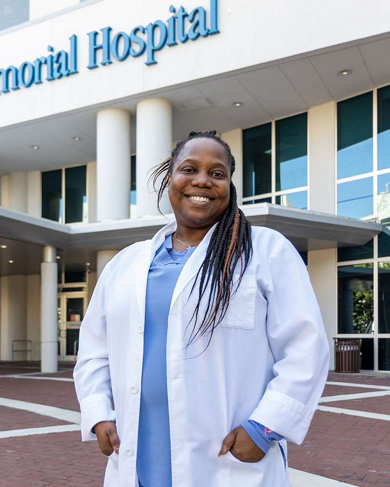 Women standing in front of a medical building, she is smiling, she has on blue scrubs and a white medical jacket