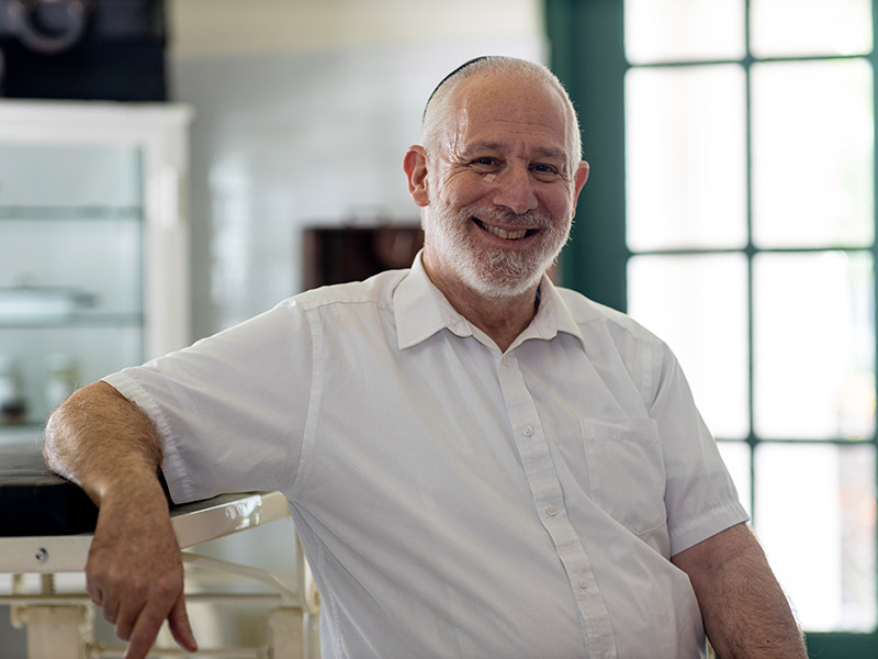 An older male sitting in a room, he wears a white shirt and smiles at the camera
