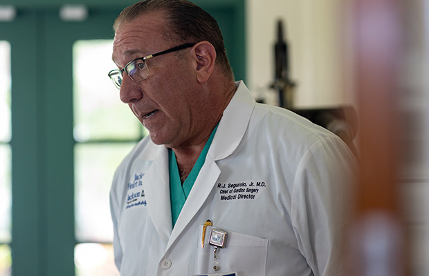 A closeup of a physician, he is wearing glasses and a white coat