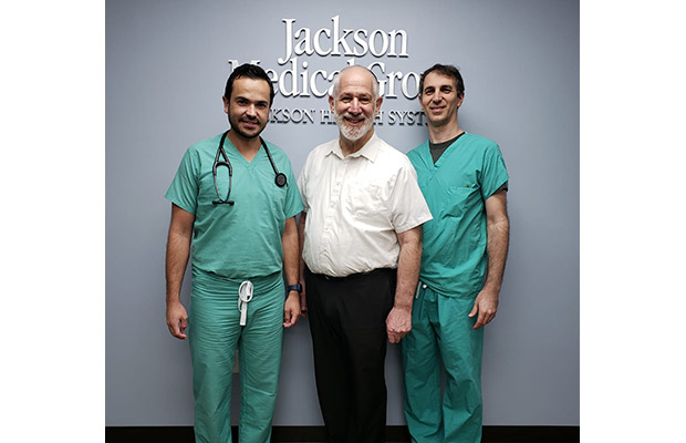 Two physicians standing next to an older male patient, they stand in front of a sign that reads Jackson Medical Group