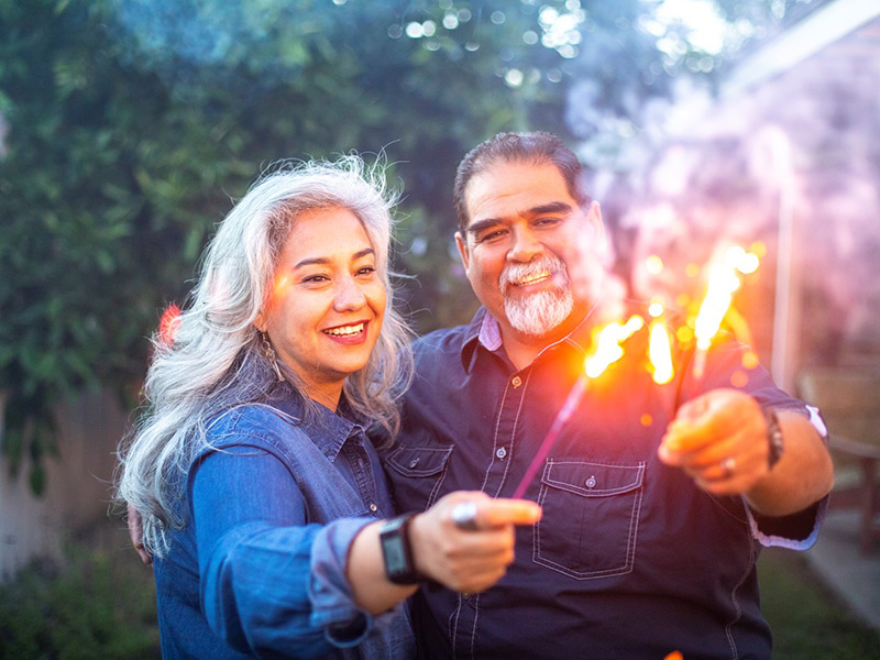 Two adults smiling outdoors, they both have an arm extended while holding sparklers