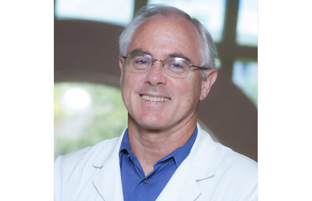 Headshot of a doctor, he is wearing a white coat, a blue shirt, has on glasses, and smiles at the camera
