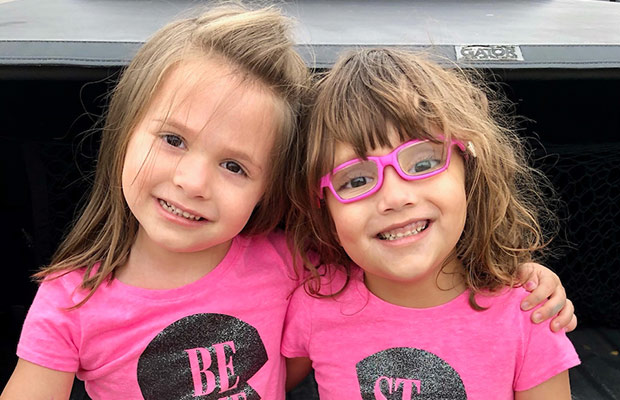 Two young girls wearing pink shirts, they smile at the camera, one young girl is wearing pink glasses