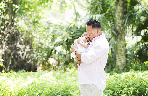 A dad holding his young daughter in his hands, they are outdoors surrounded by a lush green landscape