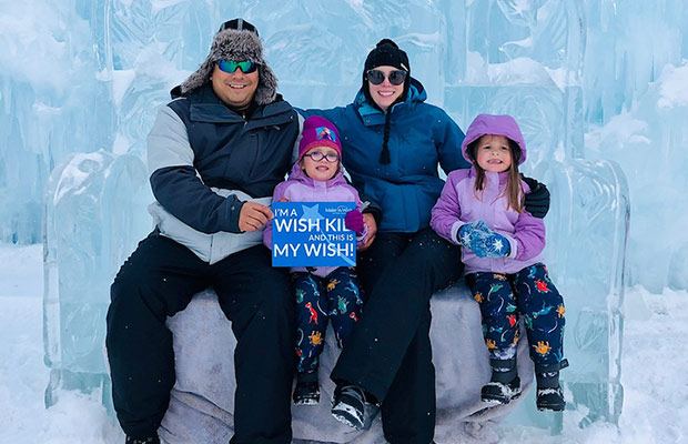 A mom and dad sitting on an ice sculpture with their two young daughters; there is a sign that reads I'm a wish kid and this is my wish!