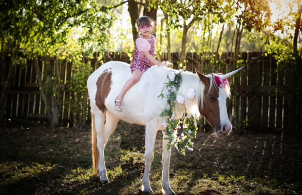Young girl on a horse, the girl smiles at the camera, the horse has flowers around its neck