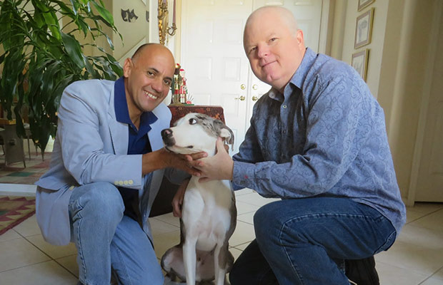 Two men kneeling and petting a dog, they both smile at the camera