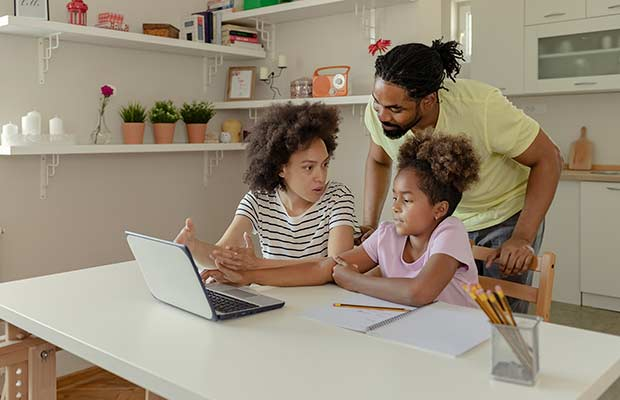 Mom and dad with their young daughter who uses a laptop for distance learning