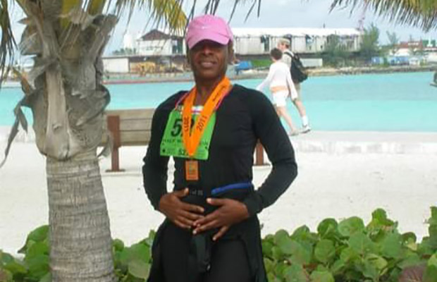 Women wearing a pink hat after a race, she had a medal around her neck, in the background you see a beach