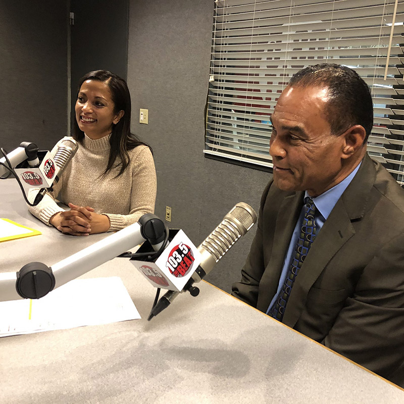 A man and woman sitting in a room and speaking into microphones