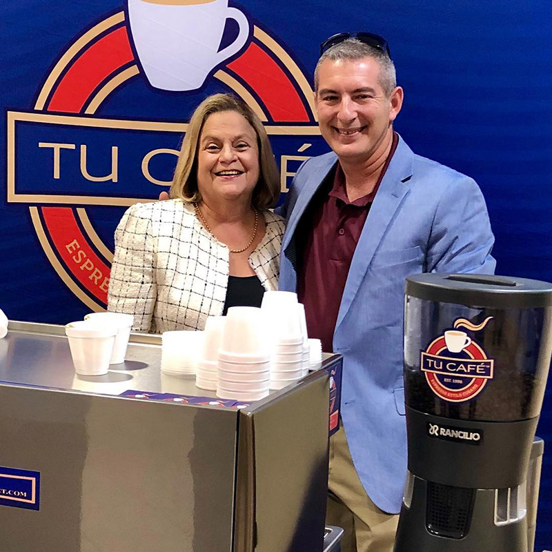 A man and woman smiling, they are standing in front of a Tu Cafe sign with coffee cups and coffee around them