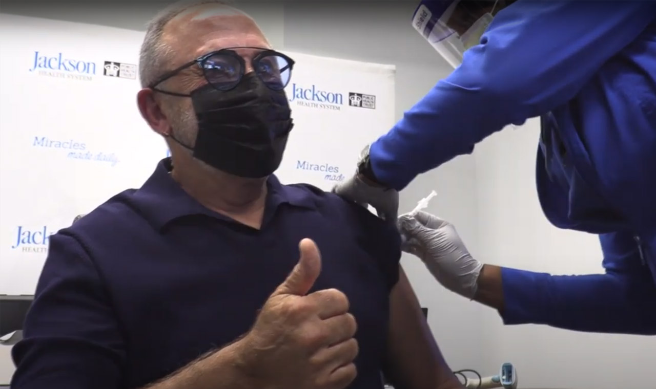 Older male with a thumbs up getting a covid-19 vaccine shot by a medical expert