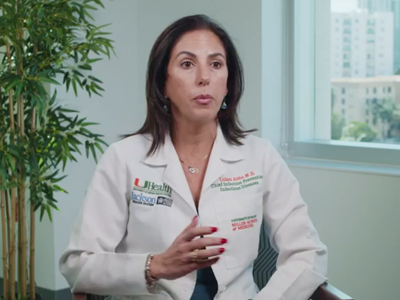 Medical expert wearing a white coat, sitting on a chair, she is speaking