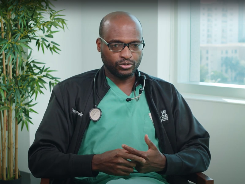 Medical expert wearing scrubs and a dark gray sweater sitting and speaking to the camera