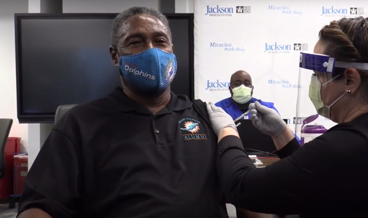 Older male wearing a Dolphins face mask getting a covid-19 vaccine shot by a female medical expert
