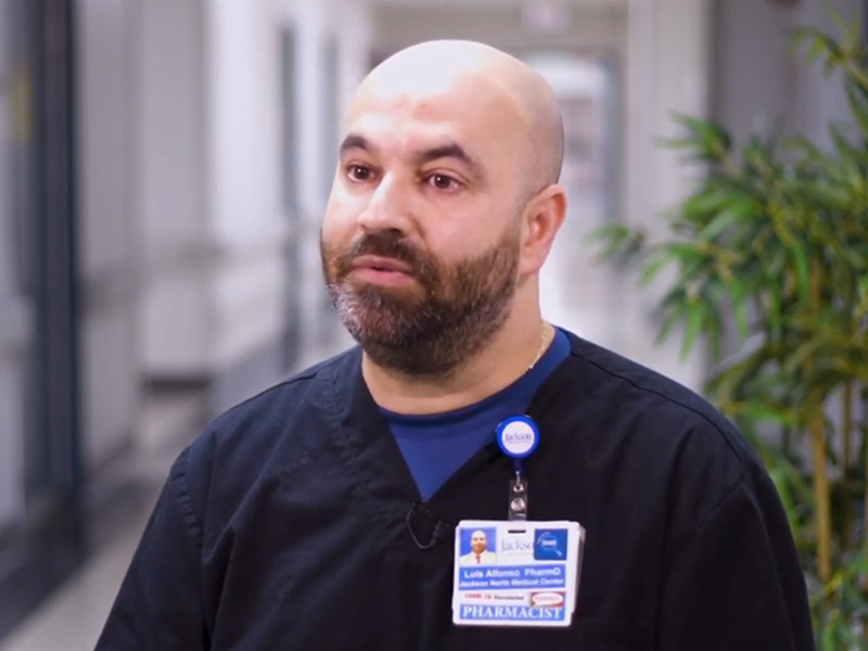 Man wearing dark blue scrubs looking towards his right, there is a tree in the background and a medical hallway