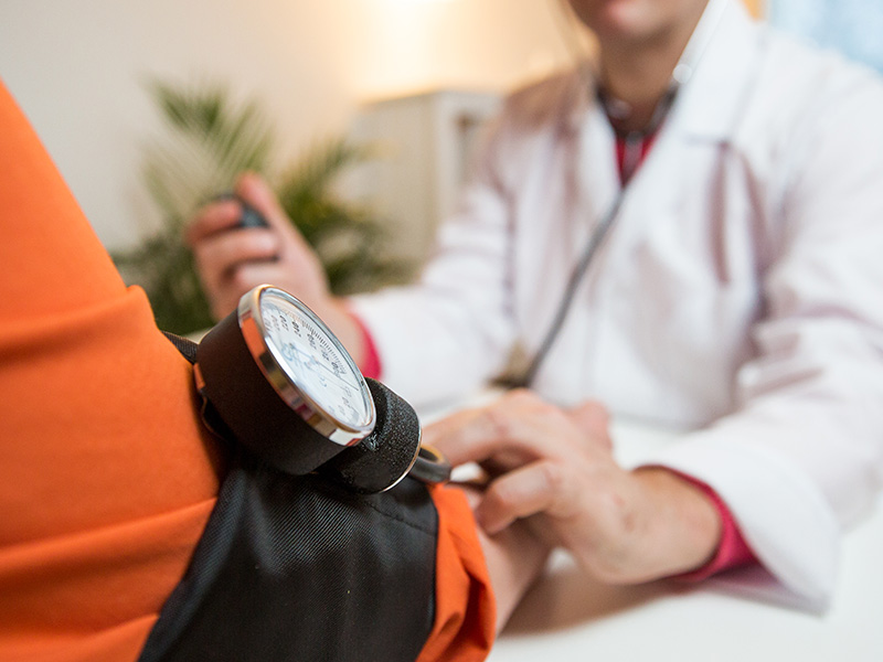 Closeup of a physician checking a patients blood pressure