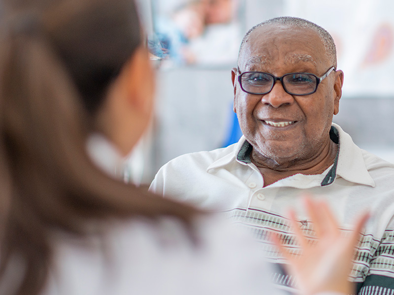 An older male smiling as he listens to his physician, you see the back of his physicians head
