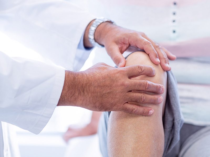 Closeup of a physician checking the right knee of a patient