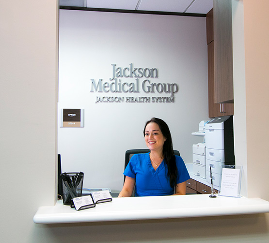 A receptionist sitting at her desk and smiling at a Jackson Medical Group location