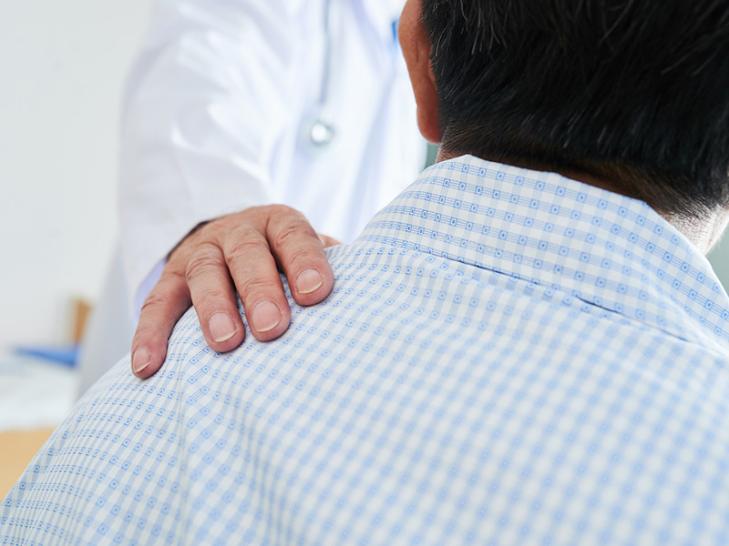 Closeup of a doctors hand on a male patients left shoulder