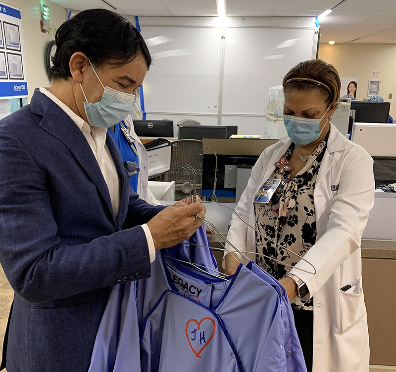 A physician looking at hospital gowns, there is a man next to her who is holding the gowns and looking down at them