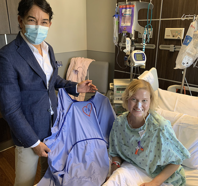 A man wearing a face mask, a suit jacket, a white dress shirt, and khaki pants is holding up a blue gown next to a woman who is smiling and sitting on a hospital bed, they both are looking at the camera