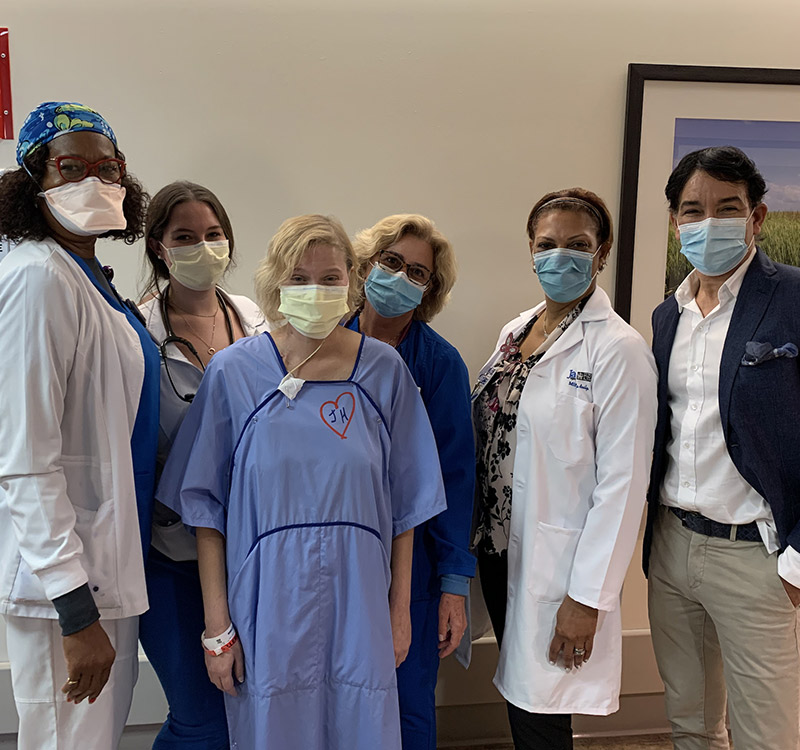 A group of medical professionals, a man, and a patient within a hospital hallway. They are all wearing face coverings and looking at the camera