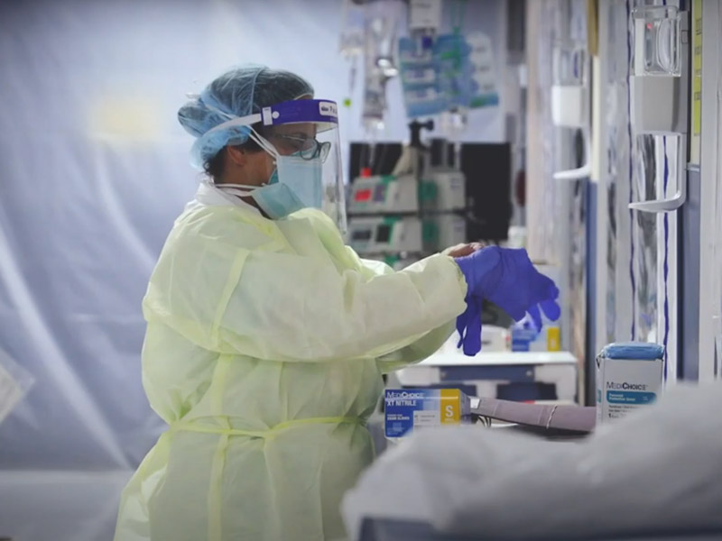 A surgeon with a multiple masks on, a hair net, and putting on gloves
