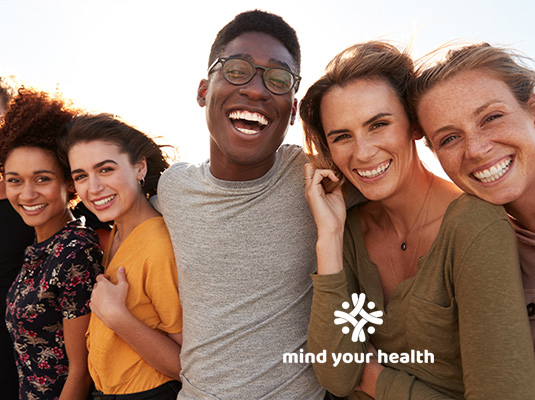 A group of young adults smiling at the camera, there are four woman and one man, they are all happy and smiling