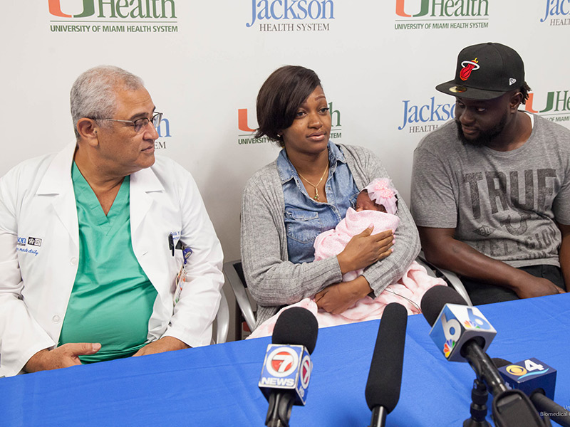 Joy Miller holding her daughter as she speaks at a press conference with her doctor and husband at her side