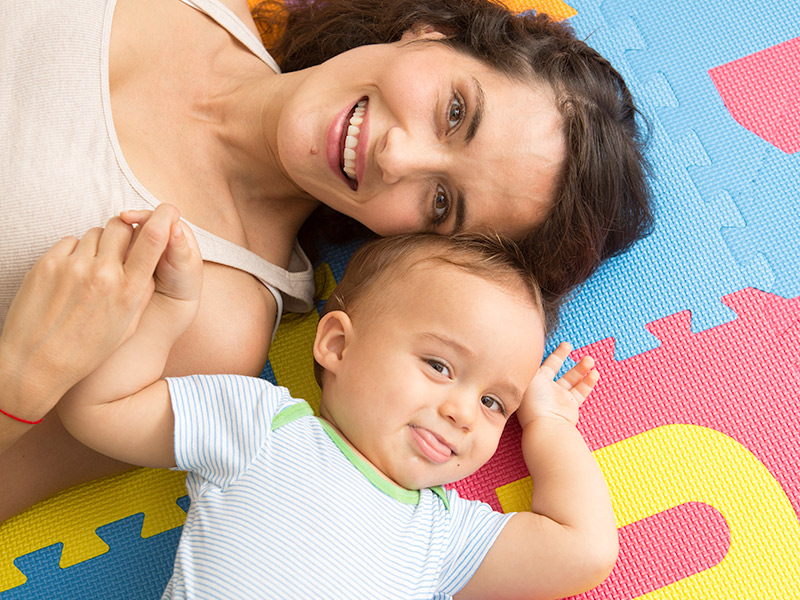 Maria and her baby smiling at the camera as they lay down on a mat and hold hands
