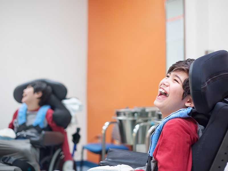 Smiling disabled little boy sitting in wheelchair at a doctor's office
