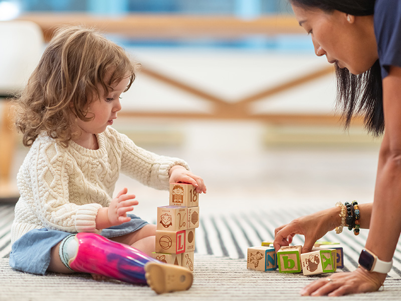 A preschool age girl with a prosthetic leg is sitting and playing with wooden blocks with a physician